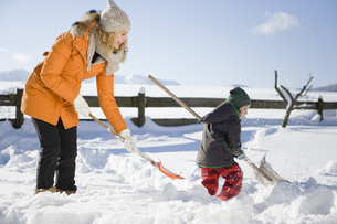 Mother and son digging with snow shovelsの写真素材 [FYI02124752]