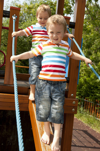 Twin brothers walking down wooden beam in playgroundの写真素材 [FYI02124766]