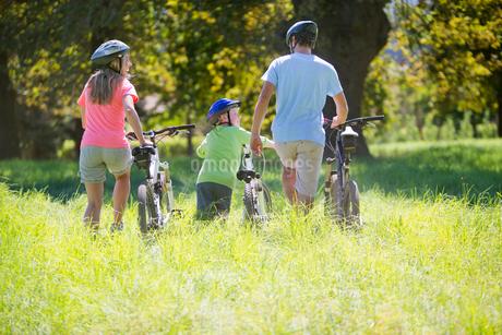 Family, pushing mountain bikes, in treelined fieldの写真素材 [FYI02124767]
