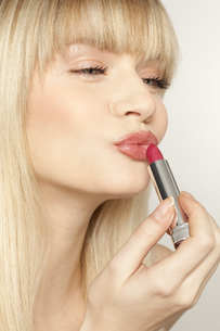 Young woman applying red lipstickの写真素材 [FYI02124770]