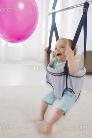 A young child in a baby bouncer looking at a pink balloonの写真素材 [FYI02124780]