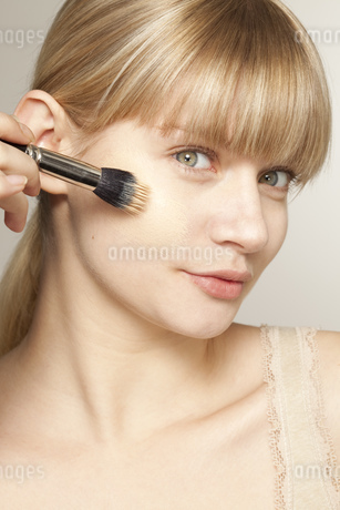Portrait of young woman applying make up with brushの写真素材 [FYI02124781]