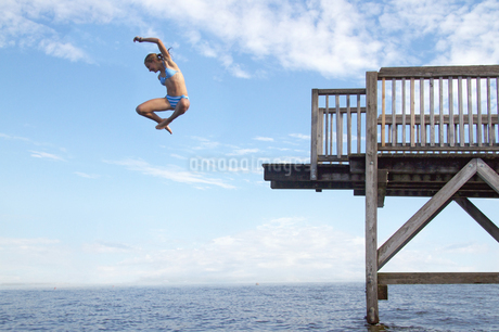 Young girl jumping into sea into pierの写真素材 [FYI02124783]