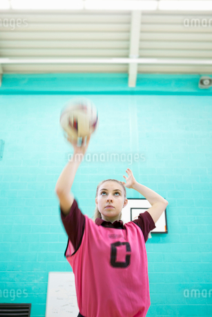 Focused high school student playing netball in gym classの写真素材 [FYI02124817]