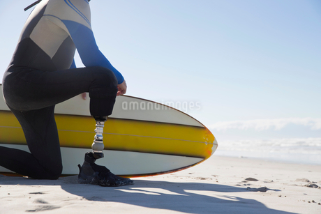 Close Up Of Surfer With Artificial Leg Kneeling On Beachの写真素材 [FYI02124829]