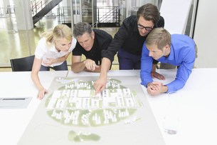 Four architects looking at architectural model in studioの写真素材 [FYI02124849]
