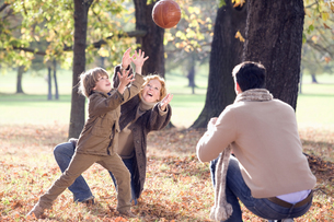 Family playing with ball in autumn forestの写真素材 [FYI02124855]