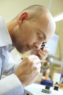 Mid adult man examining diamond in jewelry storeの写真素材 [FYI02124866]