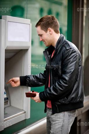 A young man using a cash machineの写真素材 [FYI02124870]