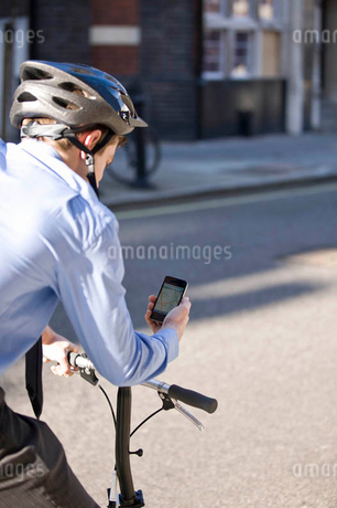 A businessman on his bicycle, looking at a map on his mobile phoneの写真素材 [FYI02124871]