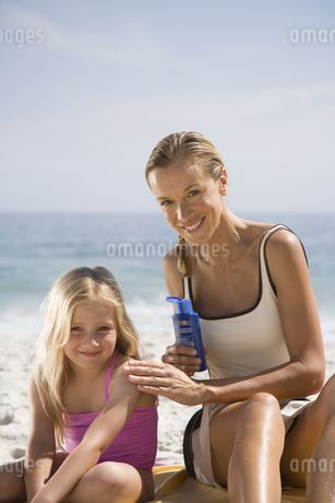 Mother putting sun screen on daughter at beachの写真素材 [FYI02124876]