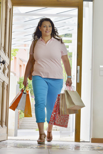 Mid adult woman arriving home with shopping bagsの写真素材 [FYI02124877]
