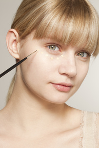 Portrait of young woman applying make up with brushの写真素材 [FYI02124900]
