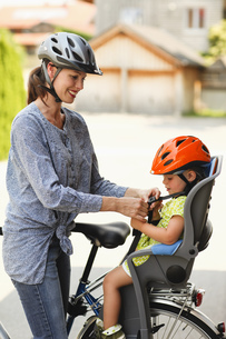 Mother strapping child in car seat on bicycleの写真素材 [FYI02124924]