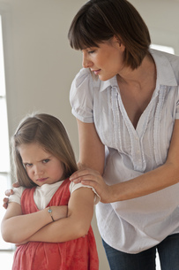 Mid adult woman consoling sulking daughter, portraitの写真素材 [FYI02124930]