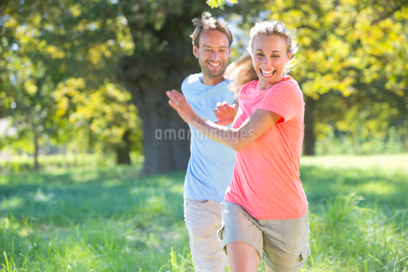 Couple, playfully chasing each other, in treelined fieldの写真素材 [FYI02124944]