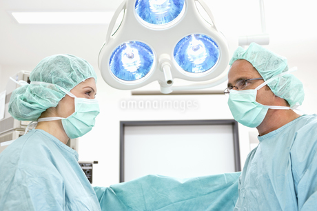 Doctor and nurse in surgical scrubs standing in operating roomの写真素材 [FYI02124946]