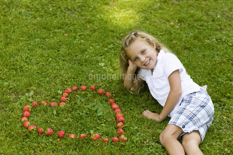 Girl posing with heart-shaped strawberriesの写真素材 [FYI02124962]