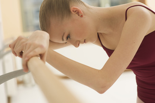 A ballet dancer leaning on the barre looking downの写真素材 [FYI02124976]