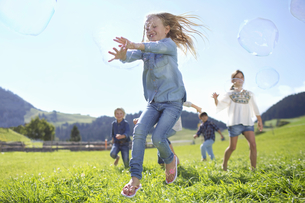 Children Chasing Giant Bubbles In Countrysideの写真素材 [FYI02125020]