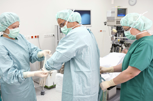 Nurses helping doctor get ready for surgeryの写真素材 [FYI02125021]