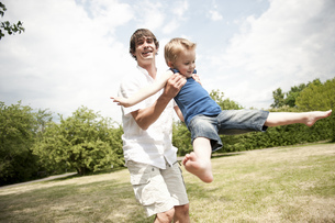father spinning son around in parkの写真素材 [FYI02125034]