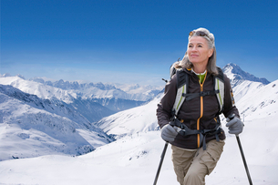 Mature Woman Hiking Through Snow Covered Mountainsの写真素材 [FYI02125049]