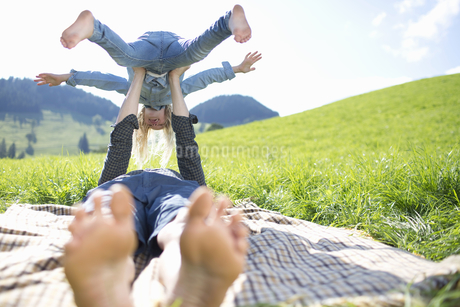 Father Balancing Daughter On Arms In Countryside Fieldの写真素材 [FYI02125067]