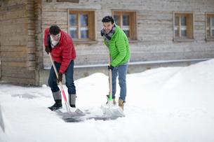 Men shoveling snow outside log cabinの写真素材 [FYI02125107]