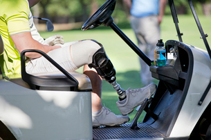 Male Golfer With Artificial Leg Driving Buggy On Golf Courseの写真素材 [FYI02125108]
