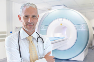 Male Radiographer Standing By MRI Scanner In Hospitalの写真素材 [FYI02125116]
