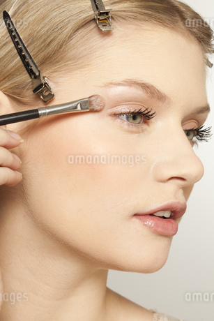 Young woman applying make up with brushの写真素材 [FYI02125131]