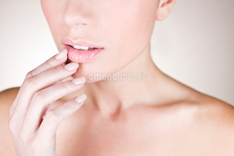 A young woman touching her lipの写真素材 [FYI02125140]
