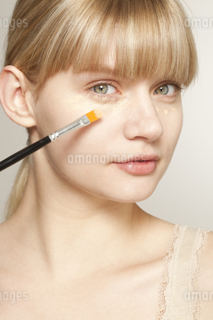 Portrait of young woman applying make up with brushの写真素材 [FYI02125148]