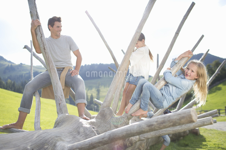Father And Children Climbing On Dead Tree In Countrysideの写真素材 [FYI02125156]