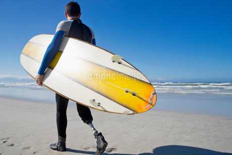 Surfer With Artificial Leg Standing On Beachの写真素材 [FYI02125159]