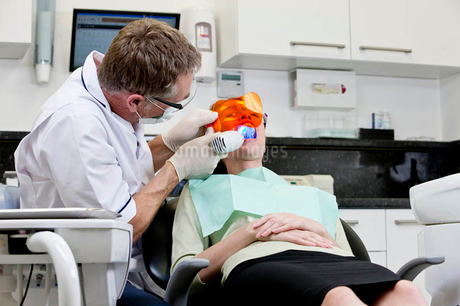 A male dentist filling a female patients teethの写真素材 [FYI02125162]