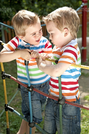 Twin brothers climbing on ropes in playgroundの写真素材 [FYI02125171]
