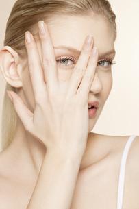 Portrait of young woman peering through fingersの写真素材 [FYI02125192]