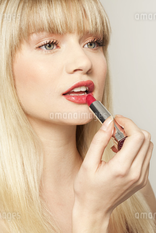 Young woman applying red lipstickの写真素材 [FYI02125198]