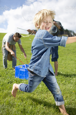 Father And Son Making Giant Bubbles In Countrysideの写真素材 [FYI02125212]