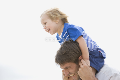 Father carrying boy on shoulders at beachの写真素材 [FYI02125221]