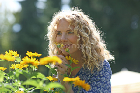 Woman smelling yellow flowers in gardenの写真素材 [FYI02125227]