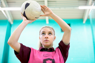 Focused high school student playing netball in gym classの写真素材 [FYI02125244]