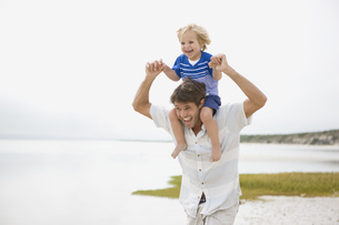 Father carrying boy on shoulders at beachの写真素材 [FYI02125259]