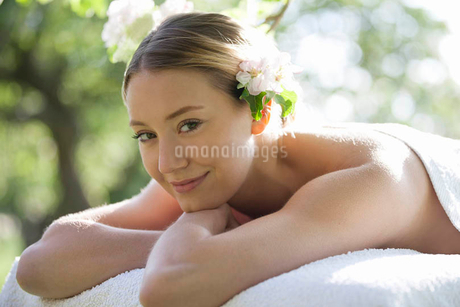 A young woman wearing blossom in her hair, smilingの写真素材 [FYI02125264]