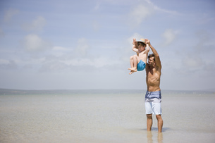 Father lifting boy above seaの写真素材 [FYI02125286]