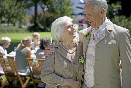 A senior couple with arms around each other at a wedding receptionの写真素材 [FYI02125302]