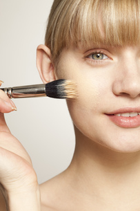 Young woman applying make up with brushの写真素材 [FYI02125304]