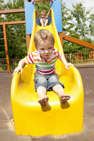 Twin brothers playing on yellow slide in playgroundの写真素材 [FYI02125311]